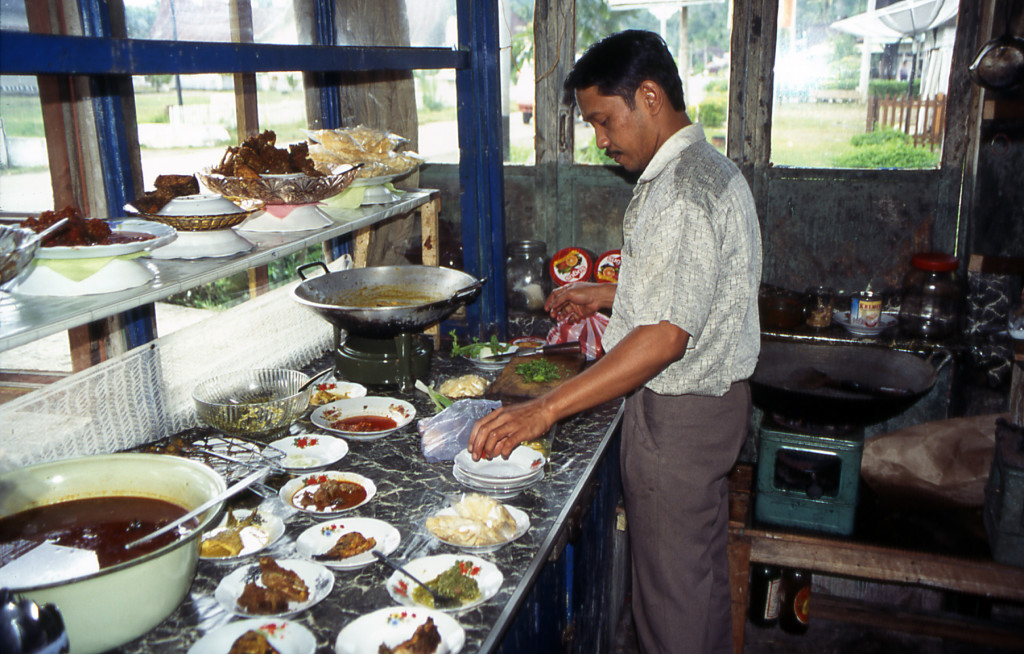 Bicycling Sumatra Restaurants prepare food and set it in windows until it is sold
